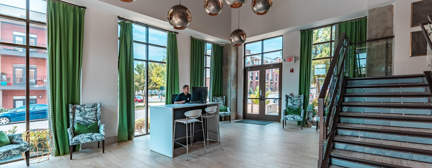 Leasing office has floor-to-ceiling windows and industrial features